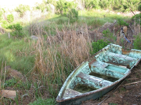 Old boat in the backyard of a house on the Grand Bayou